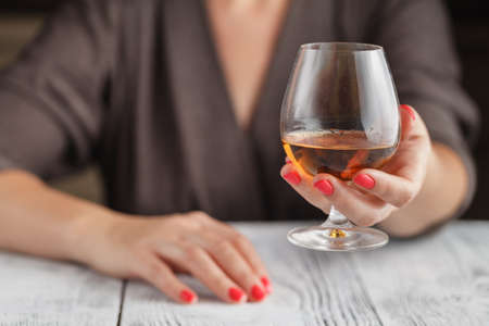 woman drinking alcohol on dark background. Focus on wine glass Stock Photo