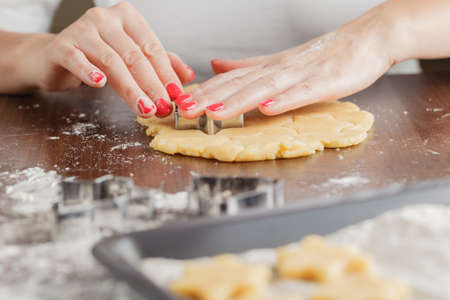 galletas de jengibre: Hand Cutting Out Shapes from Rolled Out Ginger Cookies Dough with Star Cutters
