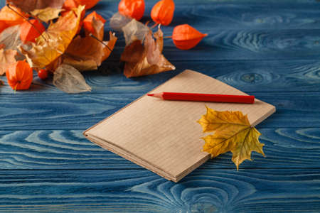 yellow notepad: Blank notepad and colorful autumn maple leaves on wooden table background
