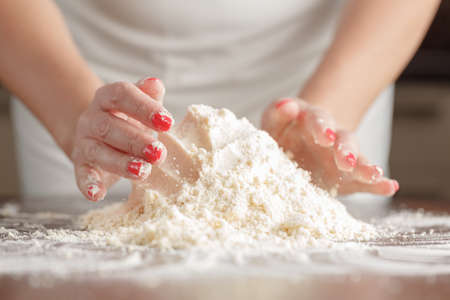 woman's hands: womans hands kneading dough on wooden table Stock Photo