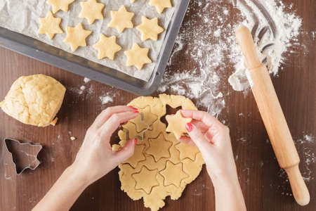 roll out: Process of extrusion gingerbread cookies in the shape of a star. Hands cooking, Moulds for cookies, roll out the dough, rolling pin, flour and parchment. View from above Stock Photo