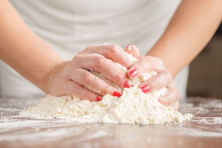 levadura: Hand of woman kneading dough for yeast cake on wooden table, preparing yeast cake