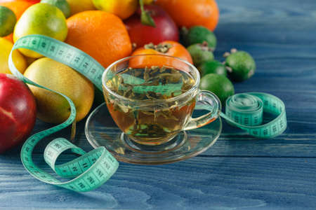 autocuidado: Concept of diet. Low-calorie fruit diet. Diet for weight loss. Plate with measuring tape and fruits on the table. Vegetarian diet for weight loss. Wellness.
