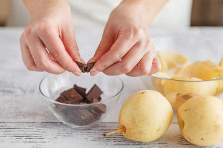 breaking: Hands breaking a chocolate in bowl