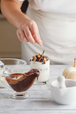 Close up on delicious peeled pear with melted chocolate on top for concept about decadent desserts