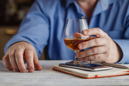 boozer: cute young man drinks whiskey at table