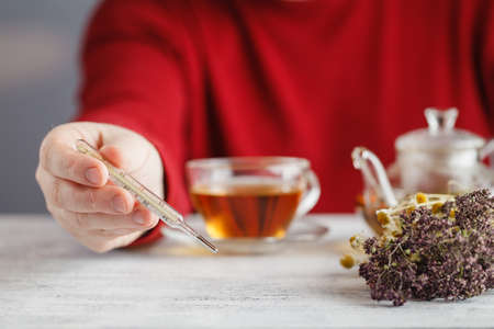 Male drink herbal tea and see thermometer Stock Photo