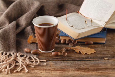 Cup of tea with old book, autumn leaves on wooden table
