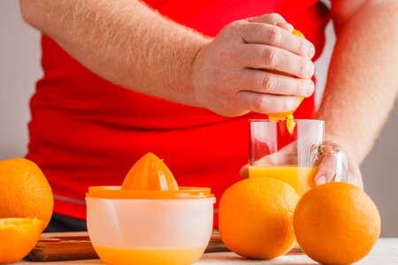 Hands make orange juice by squeezer
