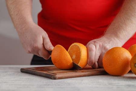 orange peel: Hand slicing orange on wooden board