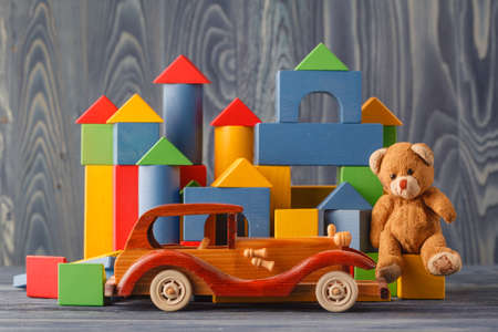 assemble: House made of wooden blocks to assemble, near a toy and a wooden toy car Stock Photo
