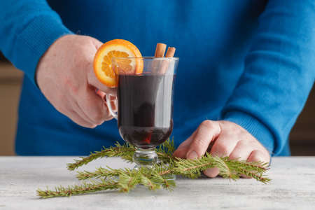 punch spice: Hands with Mulled wine and spices on old wooden table. Selective focus