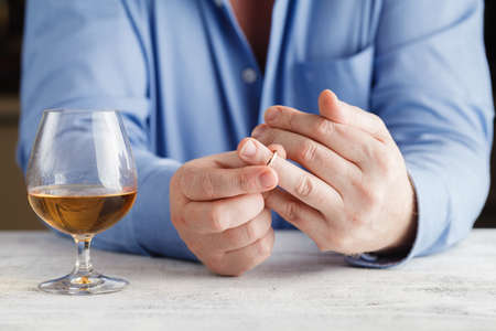 unfaithful: Divorce concept. man taking off wedding ring