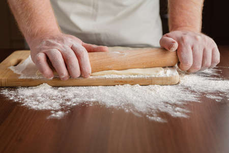 roll out: Men hands roll out dough close up. Man preparing dough for cooking pasta on a wooden table