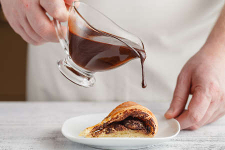 coffeetime: A piece of fresh baked delicious sponge-cake with chocolate sauce on a white plate. A hand pouring chocolate sauce out of a sauce boat on it