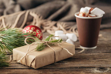 Christmas presents with rustic ribbon on dark wooden background in vintage style. Selective focus.