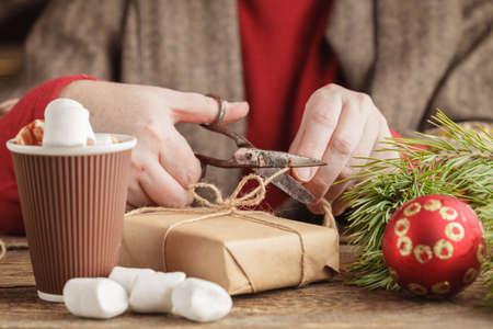christmastide: Adult man preparing thread for tying xmas gifts