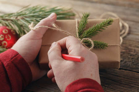 Christmas background. male hands holding New Year present. Packed gifts and scrolls, Workplace for preparing handmade decorations.