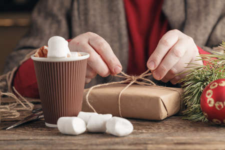christmastide: Adult man preparing thread for tying xmas gifts