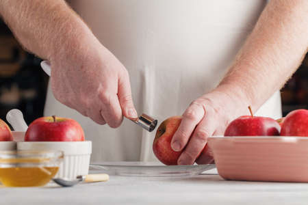 skinning: Chef hands removing pit of freshly peeled apple using a paring knife. Baking apples recipe step Stock Photo
