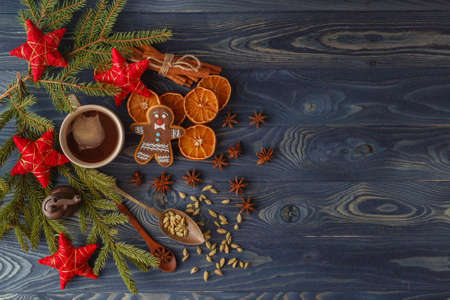 Christmas gingerbread cookies with icing, cup of tea, fir-tree branch on blue wooden background. Collection for Christmas greeting card. Copy space. Top view