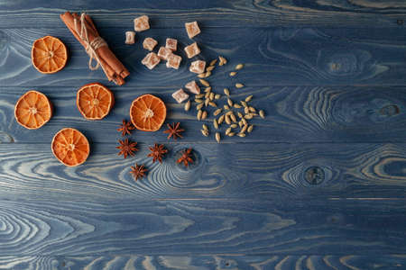 christamas: Traditional Xmas frame with spices and assorted nuts decorated with dried orange on a rustic wood background for your Christmas message