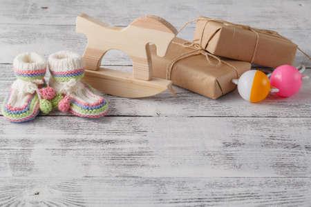 invitación del cumpleaños. Rattle, caballo de madera y botines de punto para el recién nacido