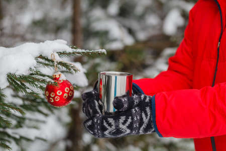 very cold: person is holding a cup of hot drink outdoor. The weather is very cold and the mug is smoking