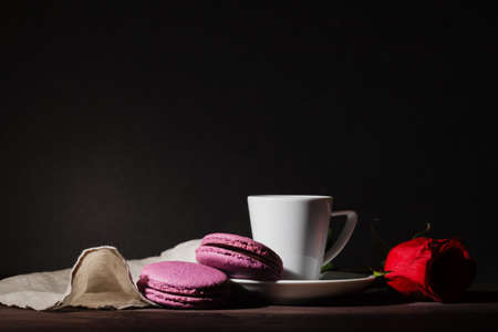 early morning: Coffee and macaroons on early morning breakfast table, dark tone