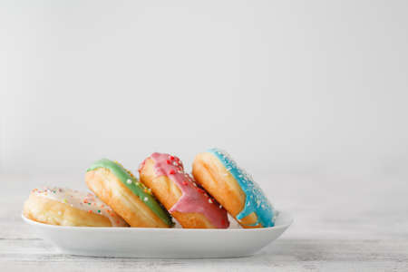 few colourfull donuts on plate