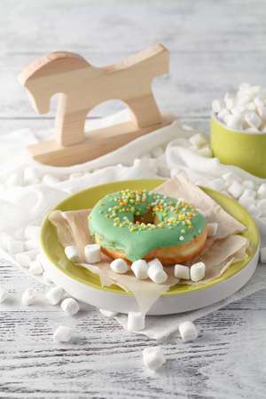 Green donuts with mini marshmallow on table Stock Photo