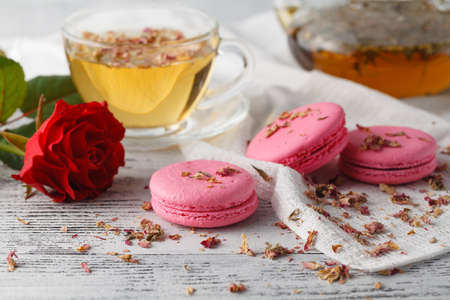 Rose petals and pink macaroons. Breakfast concept