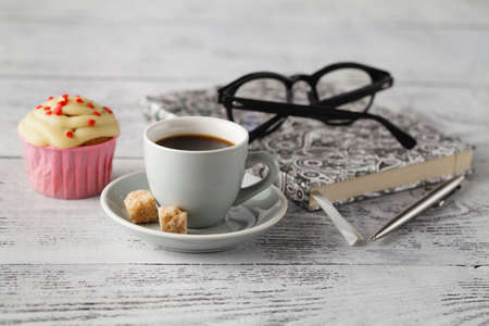 Cup of coffee and muffin on office table in begining of working day