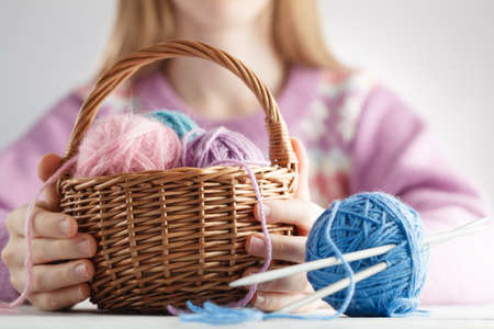 Clew of wool in basket in woman hands Stock Photo