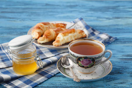 teaparty: croissant and tea in mug. Breakfast concept
