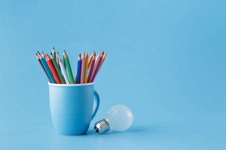 Creativity idea concept with mug o? pencils and light bulb