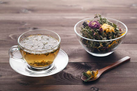 Herbal tea in glass cup on rustic wooden table
