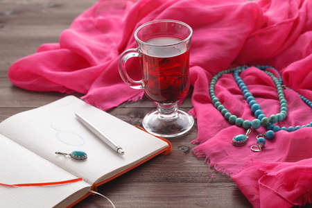 jewelry sketch in notepad on table with silk shawl and tea