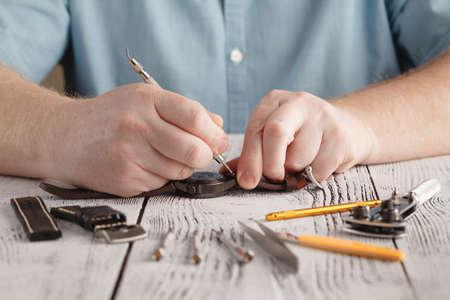 Homme répare l'horloge, bracelet de montre changé à la main Banque d'images