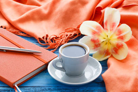 Cup of coffee on turquoise wooden table with open flower of tulip