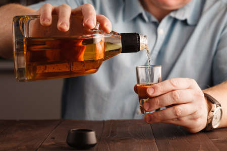 businessman celebrating by pouring more drink to himself