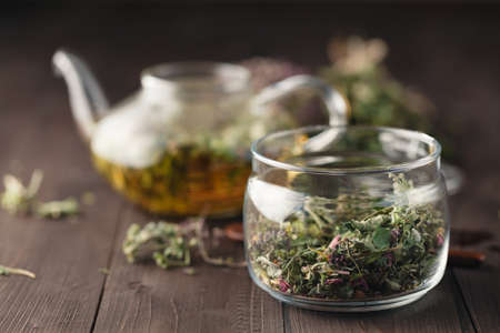 wild marjoram: Dried herbs on wooden table and kettle wfor tea