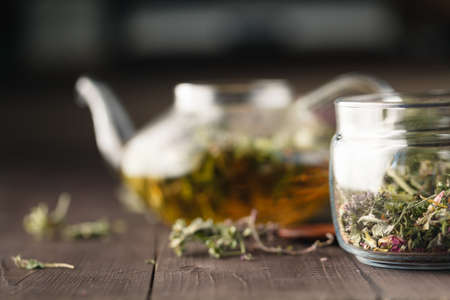 Dried herbs on wooden table and kettle wfor tea