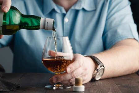 Addict issue, man pours himself a whiskey after hardwork at office