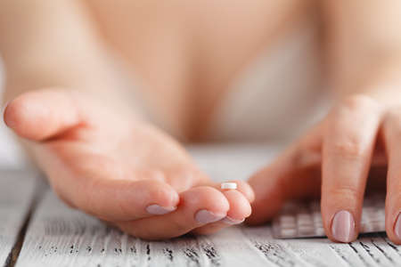 woman holding contraceptive solutions, closeup view