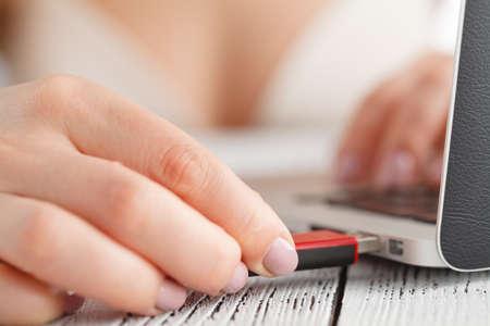 노트북 컴퓨터에 플래시 드라이브를 삽입하는 여성 손