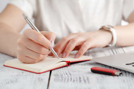 Female hands with manicure over pages of notebook hold a pen