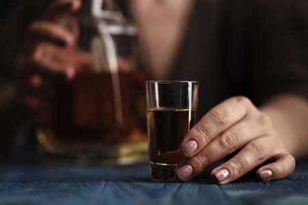 Mujer sentada en casa bebiendo demasiado whisky, ella es adicta Foto de archivo - 74963158