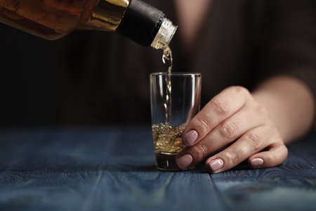 Female pouring whiskey in to glass shot