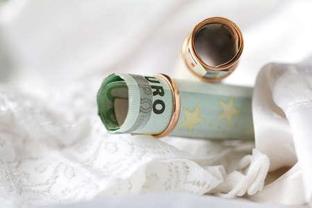 weddingrings: Wedding rings and money on a white bridal lingery background